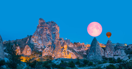 """Amazing view of Uchisar castle in Cappadocia at twilight blue hour - Girls watching moonrise at the hill of Cappadocia""""Elements of this image furnished by NASA"""""""