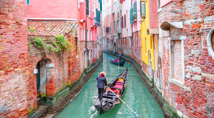 Foto auf Leinwand Rosa hell Venetian gondolier punting gondola through green canal waters of Venice Italy