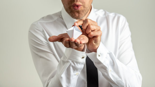 Businessman blowing in origami paper boat