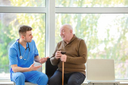 Medical worker with senior man in nursing home