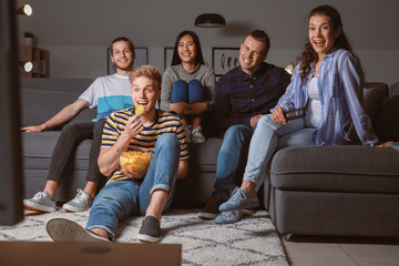 Friends watching TV at home in evening Fotobehang