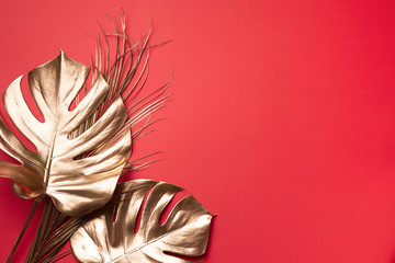 Floral minimal style concept. Exotic summer trend. Golden tropical palm monstera leaf on red color background. Shiny and sparkle design, fashion concept.