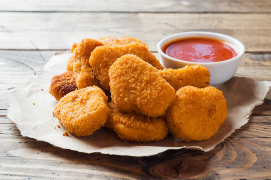 chicken nuggets with tomato sauce on wooden background. Copy space.