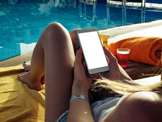 Young woman using cellphone near the swimming pool.