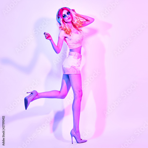 Excited fashionable DJ girl dance in colorful neon light