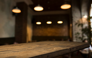 Wall Mural - Wood table top with reflect on blur of lighting in night cafe