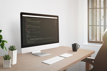 Wall Mural - Freelancer workplace concept. Computer display with open code editor. Plants, and cup of coffee on desk.