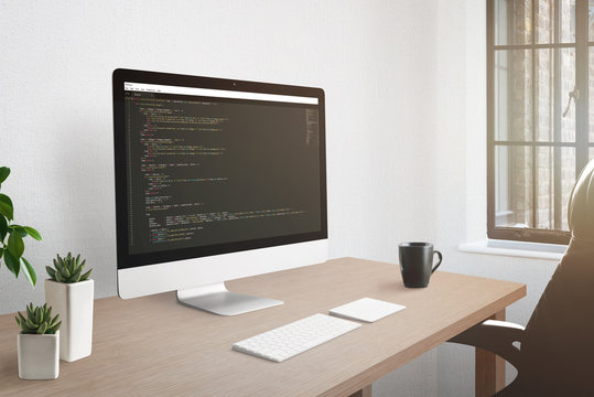 Freelancer workplace concept. Computer display with open code editor. Plants, and cup of coffee on desk.
