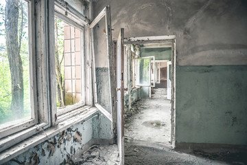 gloomy corridor with broken window frames and debris