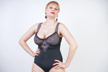 pretty short hair blonde woman with plus size body wearing retro black lingerie and posing on white studio background alone