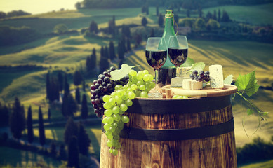 Papiers peints Vignoble Red wine bottle and wine glass on wodden barrel. Beautiful Tuscany background.