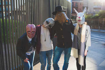 portrait of young people with funny masks standing in the street and looking camera