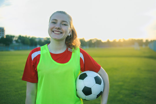 Portrait of a smiling teen girl football player with a soccer ball at sunset