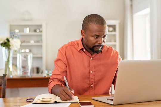 Mature man working on laptop at home