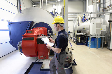 Industrial worker in a modern factory - interior closeup with machines - control of heating system boiler
