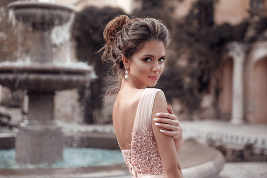 Beautiful bride with pearl earrings jewelry wears pink prom dress. Outdoor romantic portrait  of Attractive brunette woman with makeup and wedding  hair style posing at park.