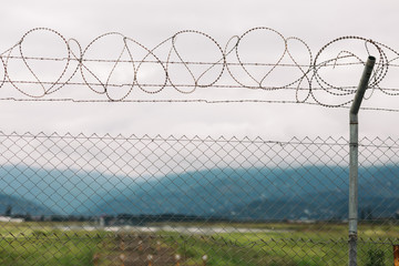 barbed wire fencing against mountains and sky background