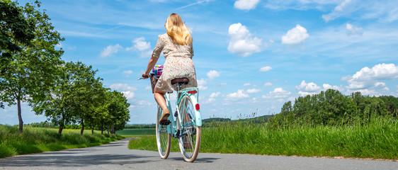 Panorama junge Frau fährt mit dem Fahrrad