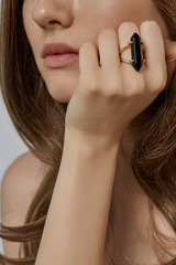 Cropped half-turn view shot of lady's face. The woman is touching her face with hand, wearing massive golden ring, adorned with black onyx gem. The girl is posing against the light gray background.