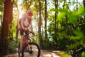 Woman cyclist bicycle riding in way of the rain forest road, adventure woman riding mountain bike alone in forest at countryside Fototapete