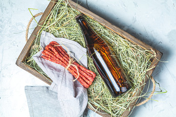 Craft beer with sausages kabanosi on gray surface
