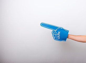Handsome fan hand glove with foam finger, pointing away over white wall background