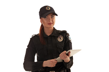 Close-up shot of a redheaded female police officer posing for the camera isolated on white background.