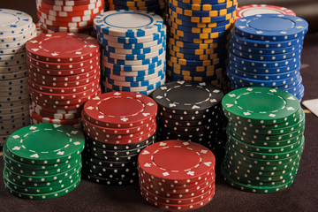 Close-up shot of a poker chips stacks standing on a table in casino.