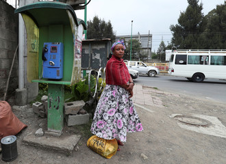 A pedestrian stands next to a telephone booth in Addis Ababa