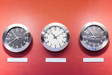 Three clocks on red wall showing different time.