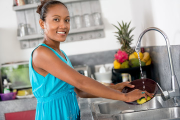 Smiling woman standing front of kitchen sink  washing dishes