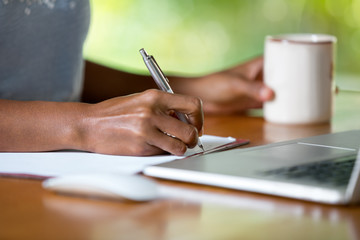 hands of businesswoman with laptop writing