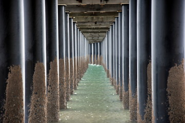 Under Urangan pier perspective view. Under a pier in Hervey Bay (Queensland, Australia), showing the structure of the pilings and support structure.