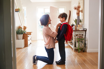 Single Mother At Home Getting Son Wearing Uniform Ready For First Day Of School Wall mural