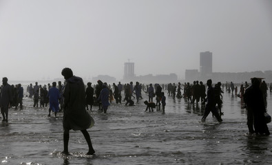 People are silhouetted as they visit Clifton beach during intense hot weather on the third and last day of the Muslim holiday Eid al-Fitr in Karachi,