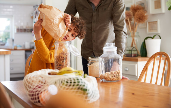 Father Helping Son To Refill Food Containers At Home Using Zero Waste Packaging