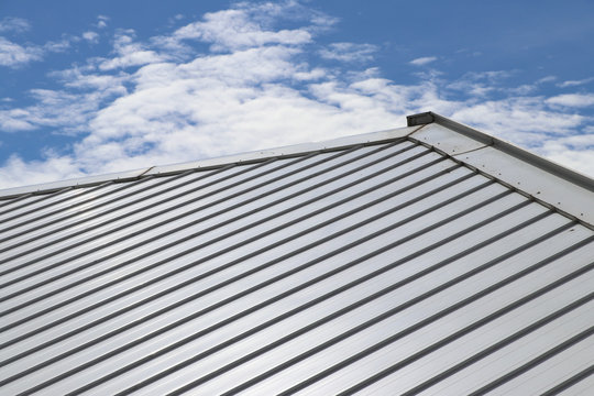Metal sheet roof and slope with clouds and blue sky background.