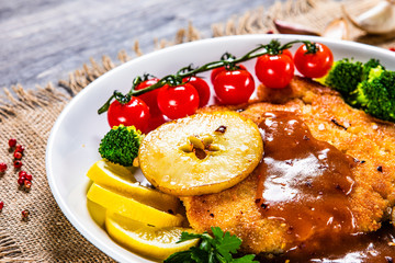 Fried pork chop with vegetables and mushrooms on wooden background