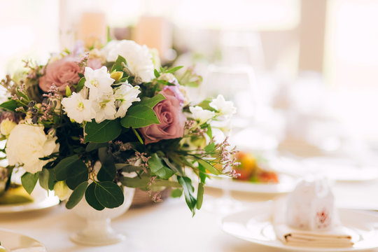 Gorgeous luxury wedding table arrangement, floral centerpiece close up. The table is served with cutlery, crockery and covered with a tablecloth. Wedding party decoration with pink and white flowers.