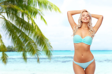 summer holidays, vacation and travel concept - young woman posing in bikini over tropical beach background in french polynesia
