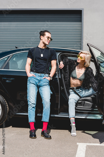 stylish handsome man and beautiful girl in sunglasses posing