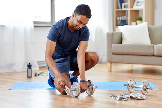 fitness, sport, weightlifting and bodybuilding concept - smiling indian man assembling dumbbells at home