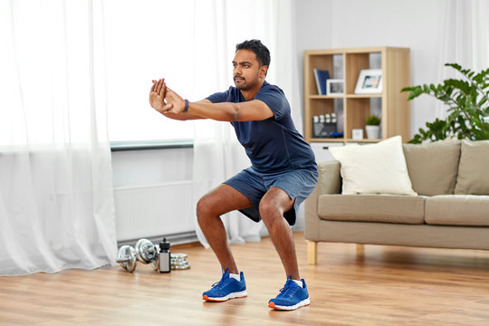 sport and healthy lifestyle concept - indian man with fitness tracker exercising and doing squats at home