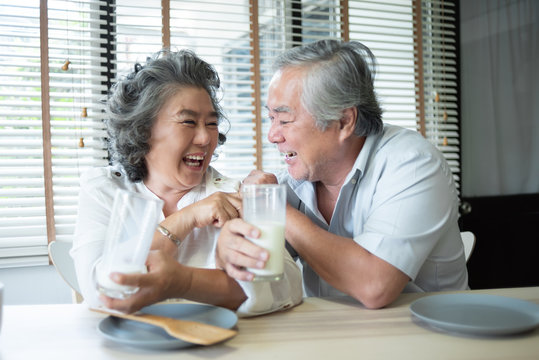 Asian senior couple in love drinking milk.