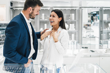 Beautiful couple enjoying in shopping at modern jewelry store. Young woman try it out gorgeous necklace and earrings.