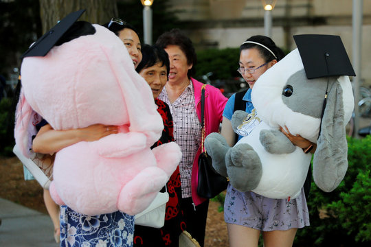 Family and friends of a student carry stuffed animals wearing graduation caps before Commencement Exercises at MIT in Cambridge