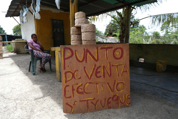 A woman sales 'Casabe', a kind of a flatbread made of yucca, next to a sign reading 'Sale point, cash and barter' near a road in Cupira