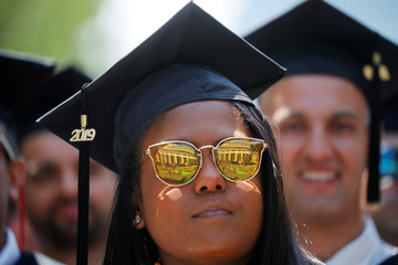A graduating student listens as former New York City Mayor Michael Bloomberg delivers the Commencement Address at MIT in Cambridge