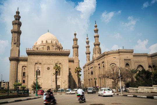 Traffic driving past The Mosque-Madrassa of Sultan Hassan, Mokattam Hill, Cairo, Egypt