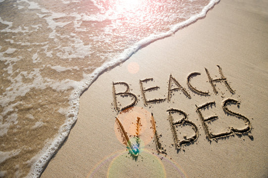 Beach Vibes tropical vacation message handwritten on smooth sand with incoming wave